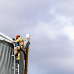 Two firefighters in PPE scaling a grain bin as part of grain bin safety training